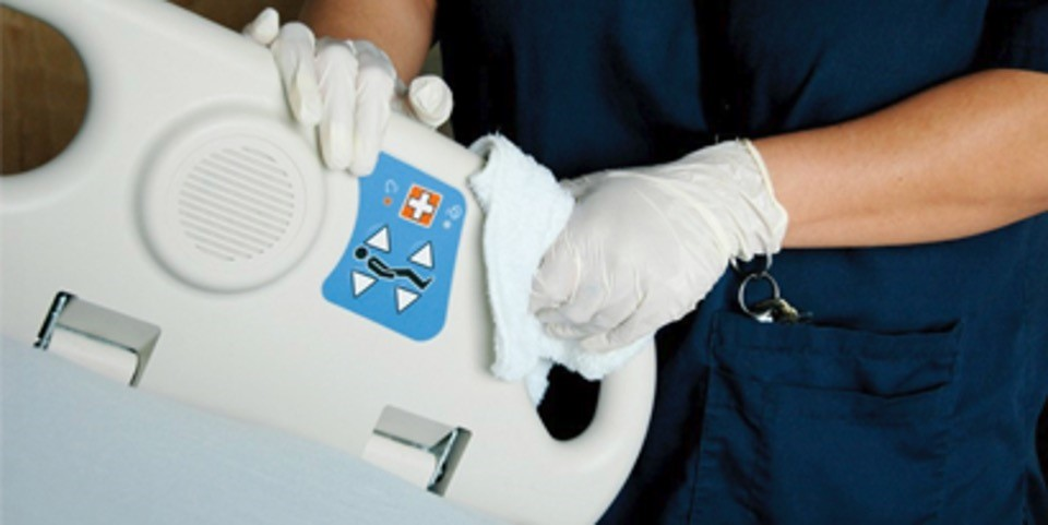 worker wearing medical gloves cleaning hospital equipment